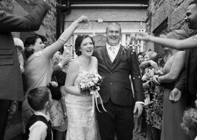a bride and groom walking through confetti at Chateau Rhianfa