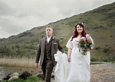 bride and groom walking by Llyn Gwynant Barns