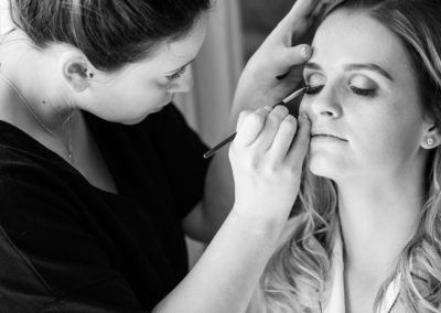 bride having makeup applied at Pentrehobyn Hall