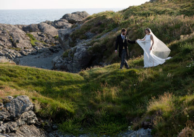 Bride and groom walking on cliffs in Trearddur Bay