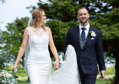 Bride and groom walking through gardens at Pentrehobyn Hall
