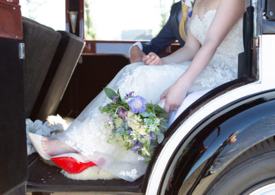 bride's bouquet lying close to a pair of Louboutin shoes