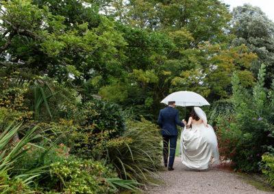 bride and groom walking under a white umbrella in Chateau Rhianfa's gardens