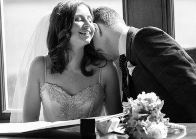 a groom at Chateau Rhianfa kissing his bride's shoulder