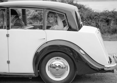 the bride looking through the wedding car at Penmon Priory