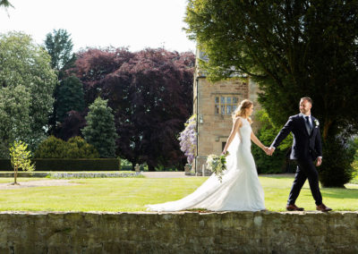 bride and groom walking in the sunshine at Pentrehobyn Hall