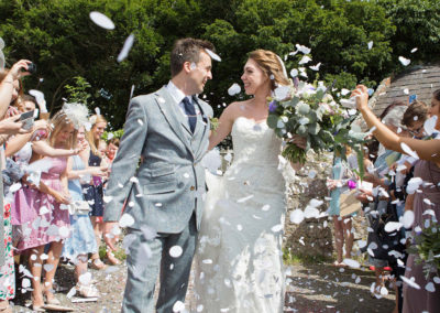 bride and groom walking through confetti at Llanedwen, Anglesey