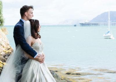 bride and groom hugging looking out at the Menai Straits at Chateau Rhianfa