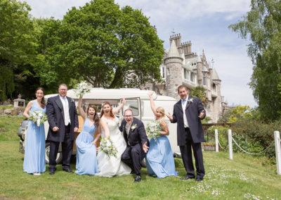 Bridal party posing infront of VW van at Chateau Rhianfa