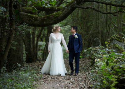 bride and groom walking through a forest at Penrhos Nature reserve, Holyhead