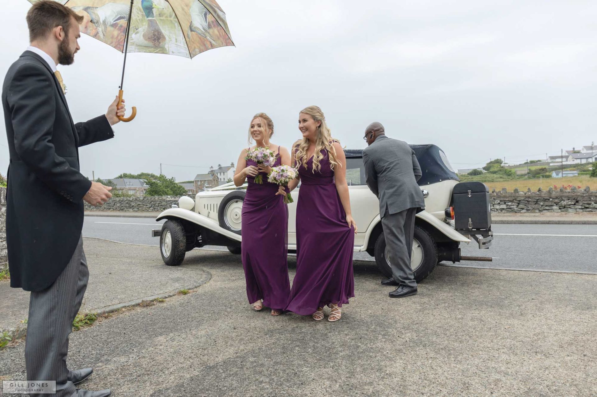 two bridesmaids are greeted by a groomsman at a Anglesey wedding
