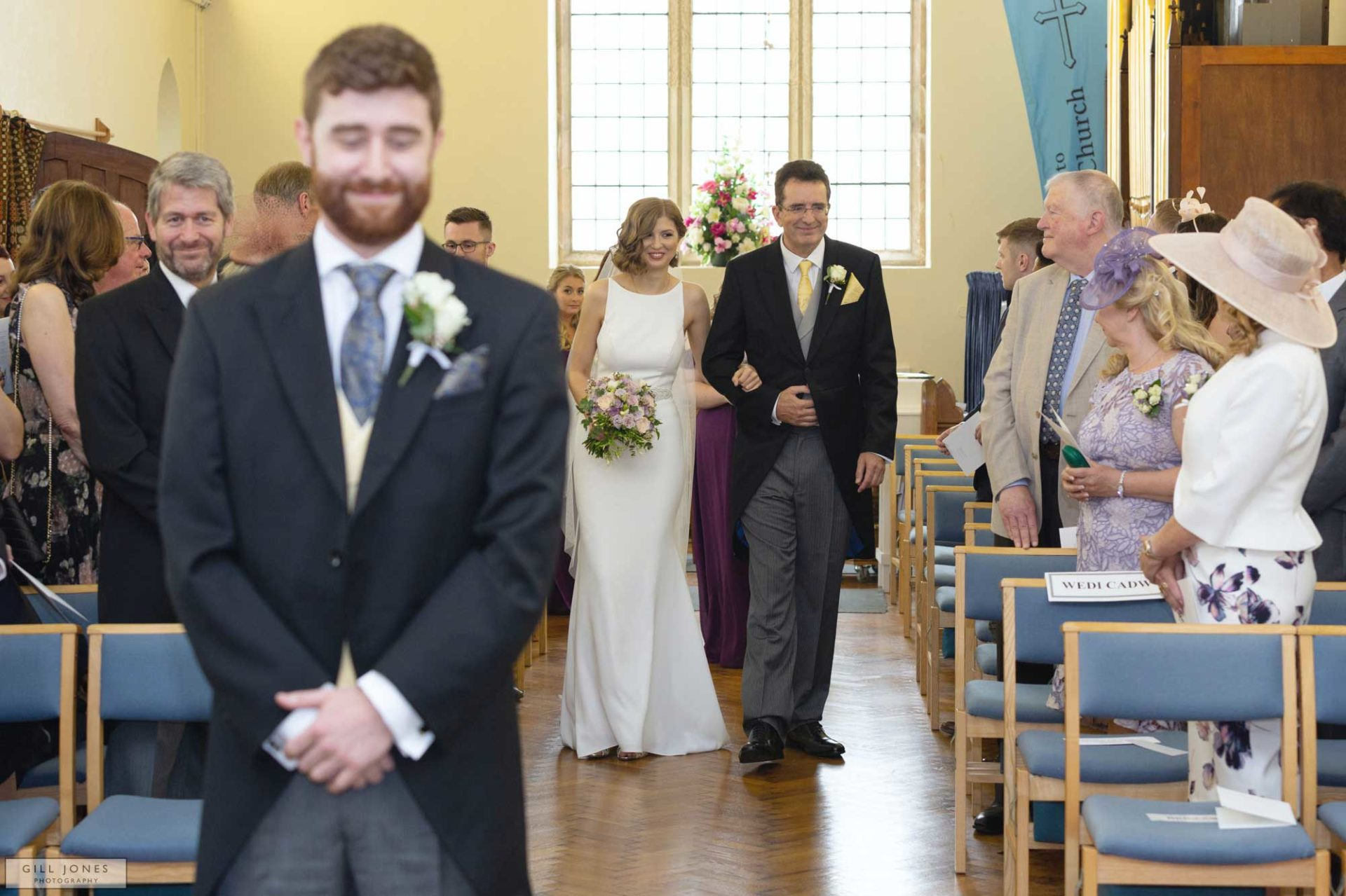 the bride is approaching her grrom up the aisle of St. Ffraids in Trearddur Bay