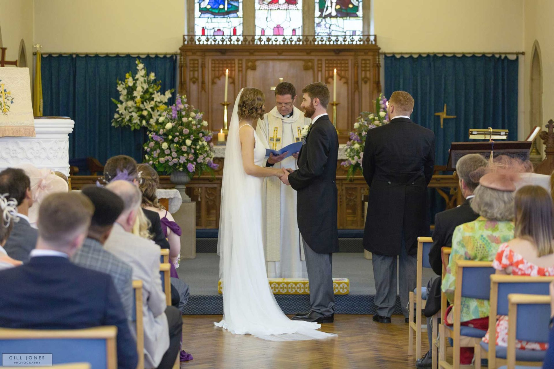 the bride and groom are repeating their vows to one another in St. Ffraids church, Trearddur Bay
