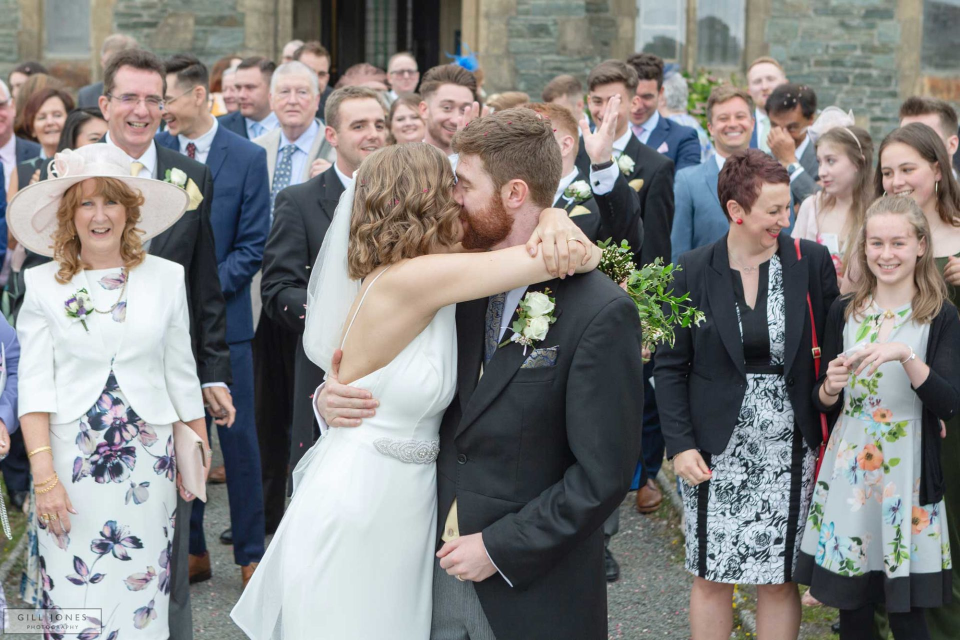 the bride and grrom are kissing each other infront of their guests outside St. Ffraids church in Trearddur Bay