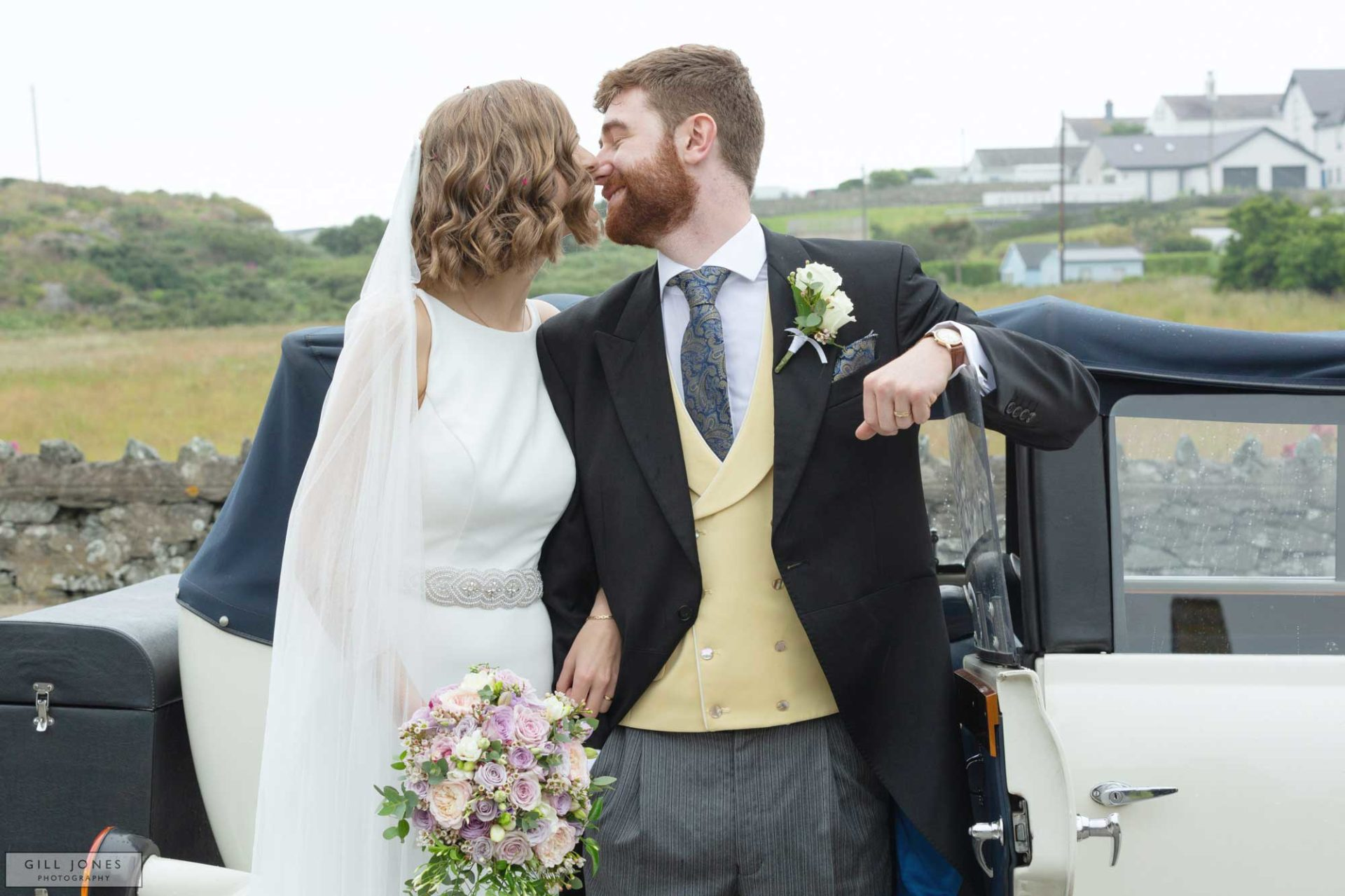 the bride and groom are just about to kiss whilst standing by a vintage wedding car