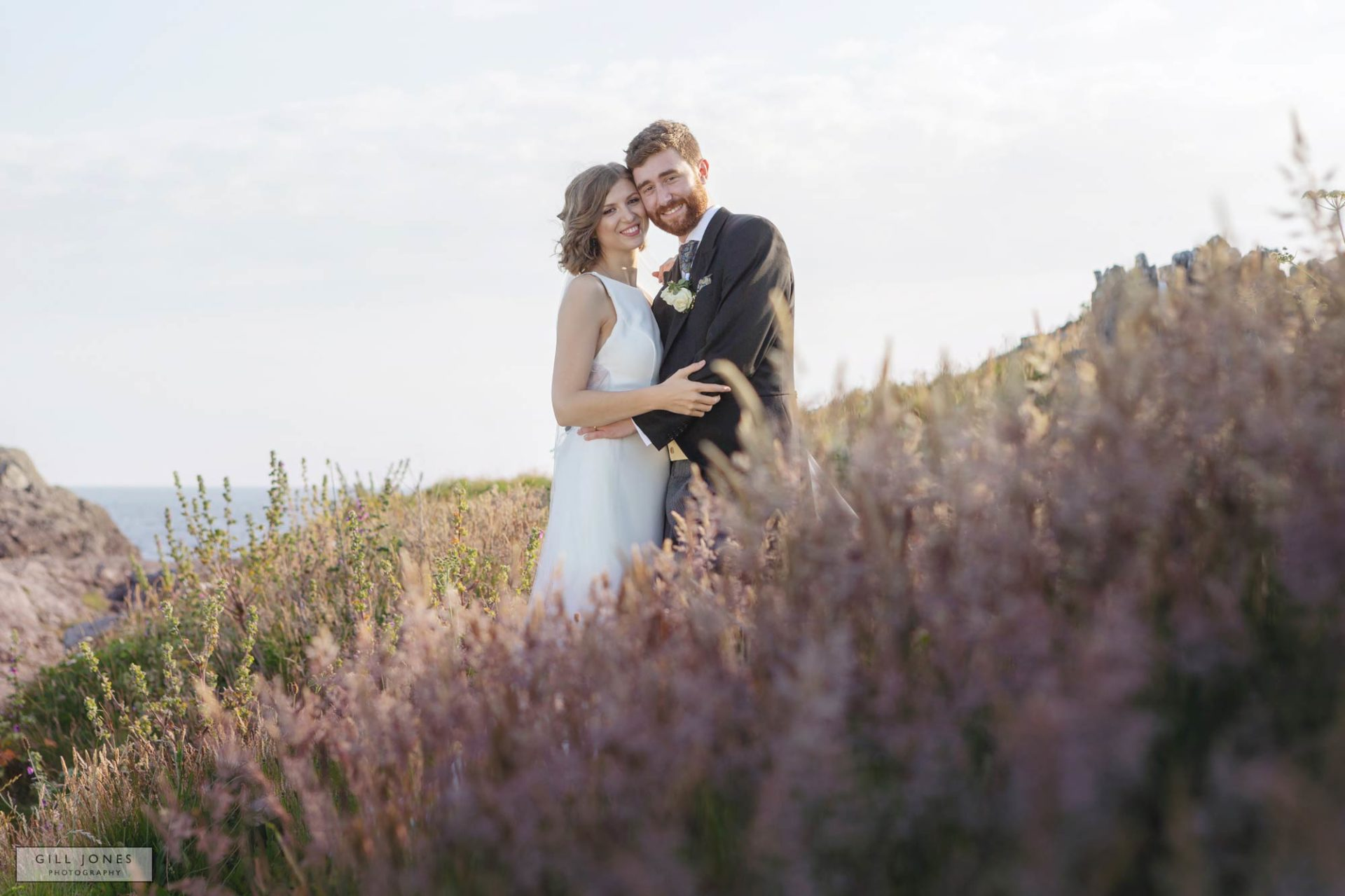 a bride and groom are caressing within pink heather