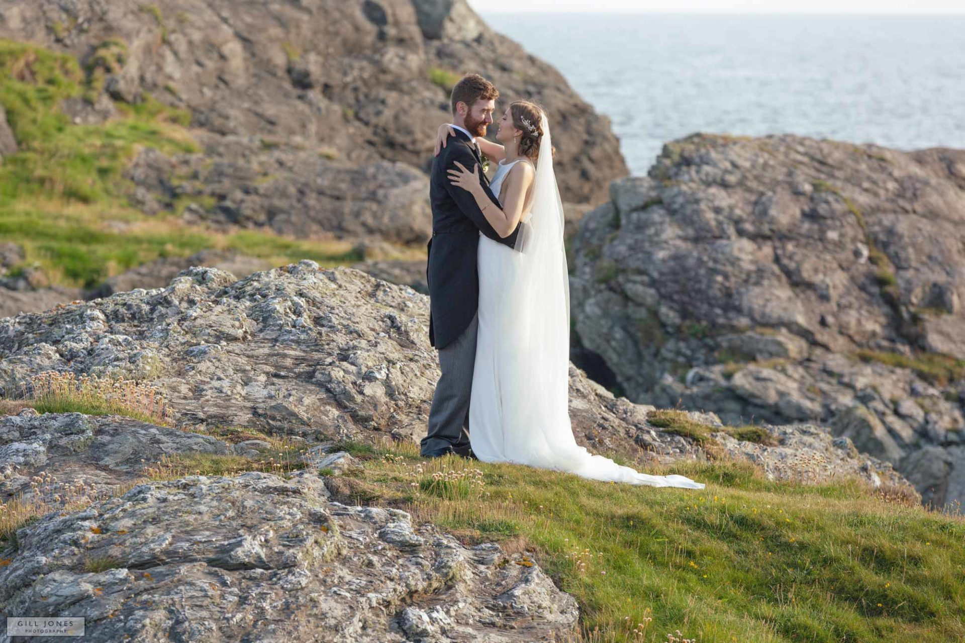 a bride and groom hugging on the rocks in trearddur bay