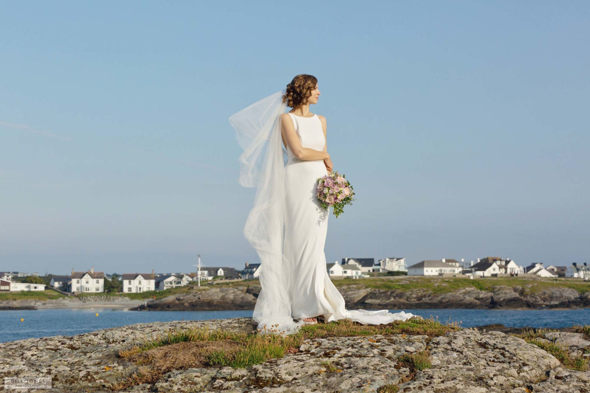 a bride standing on the rocks in trearddur bay the wind is blowing her veil