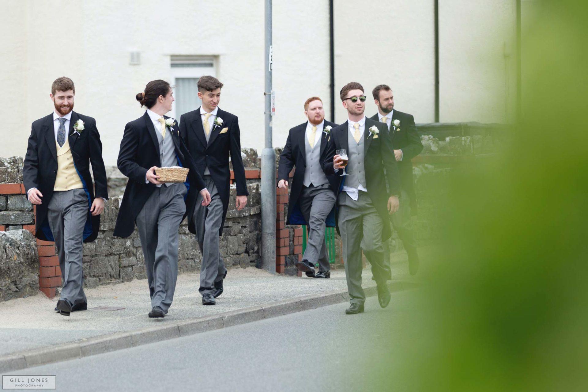 grooms men are walking along the road in Trearddur Bay towards St. Ffraids church