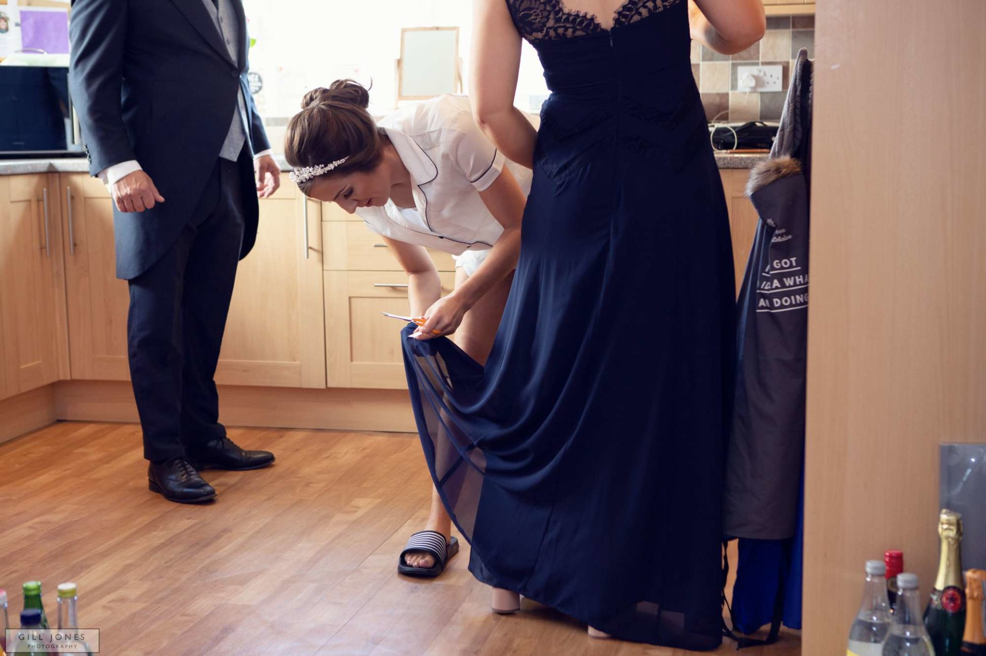 the bride cutting tags off bridesmaids dresses