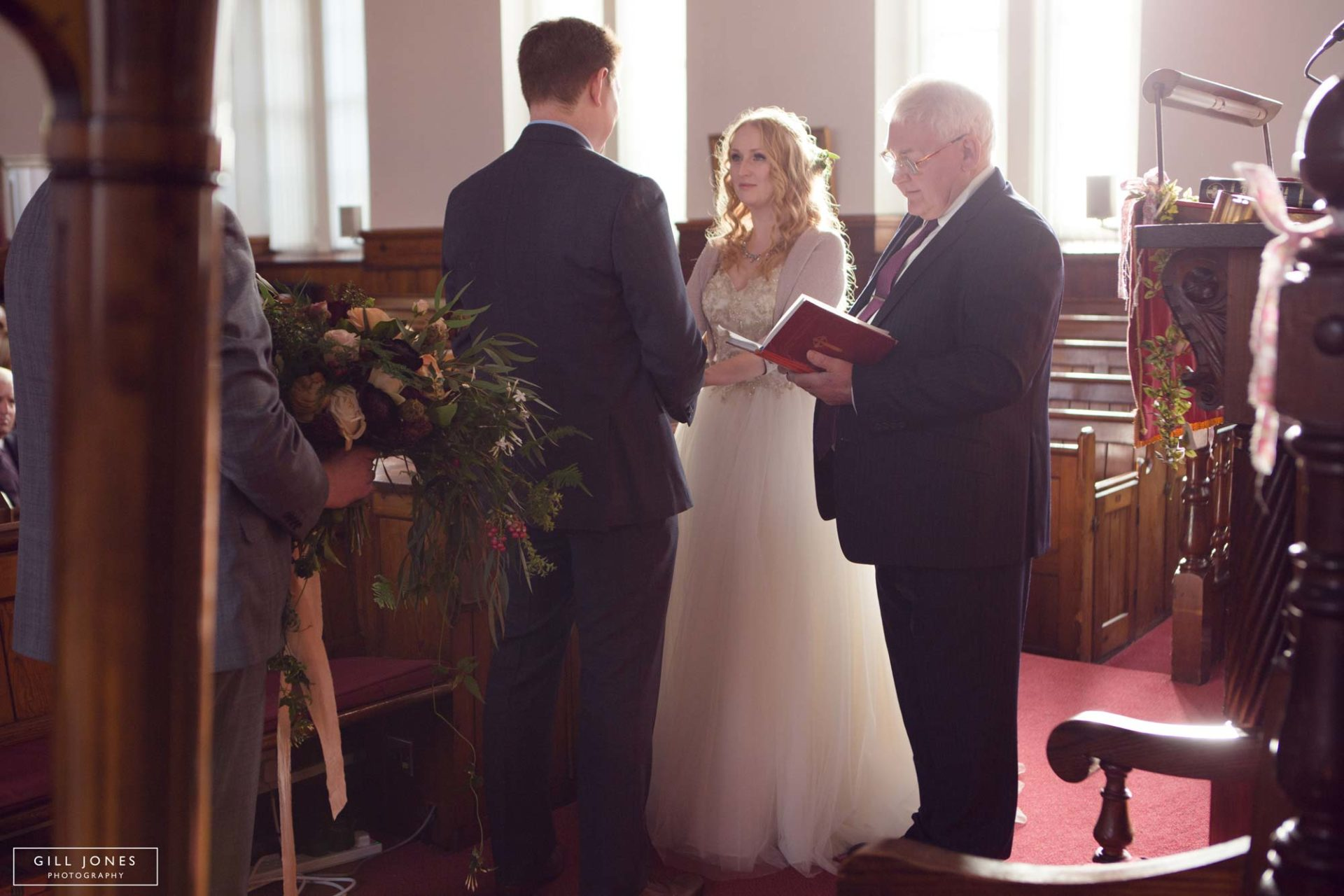 the bride and groom exchanging their vows
