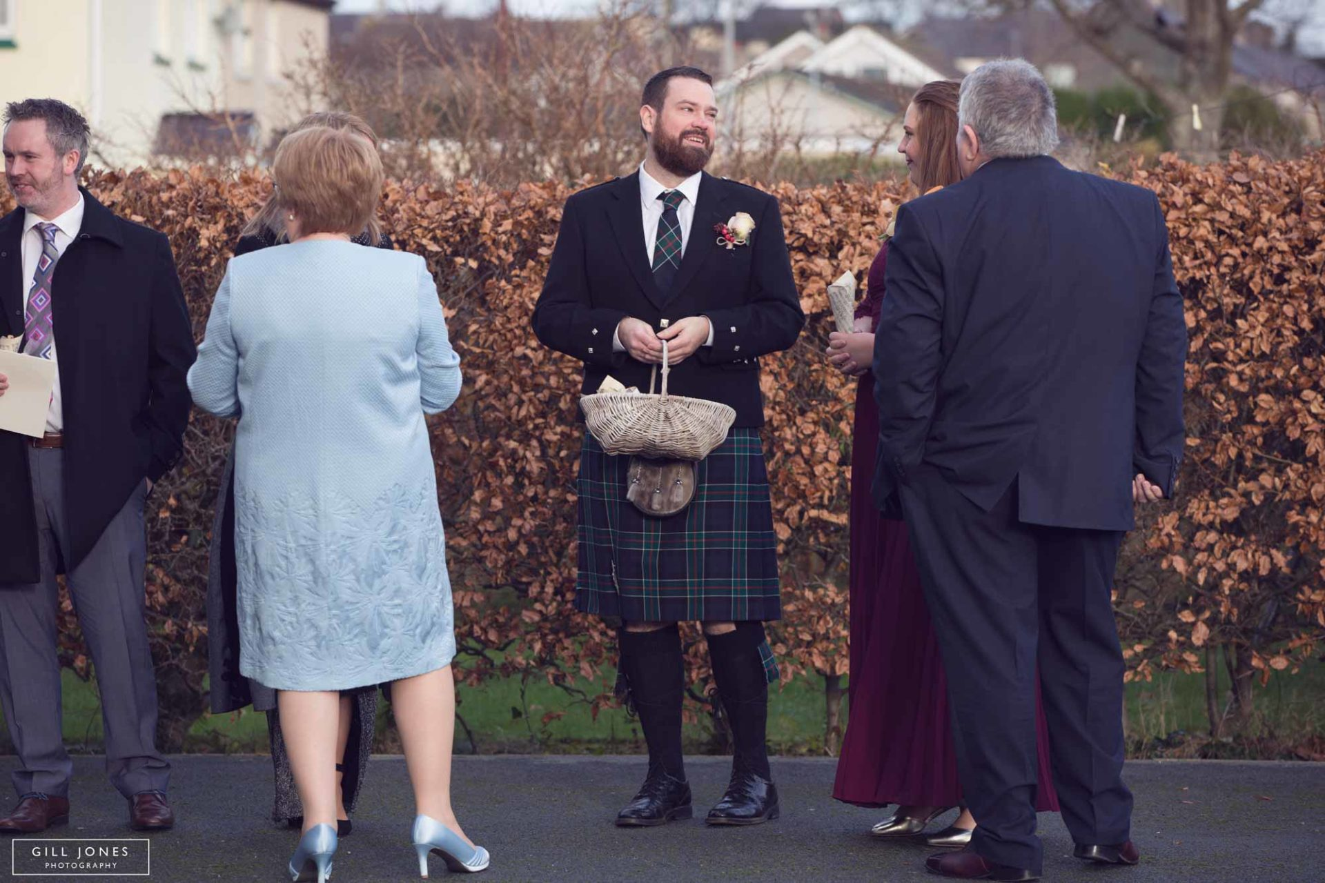 a groomsman holding a basket of flowers