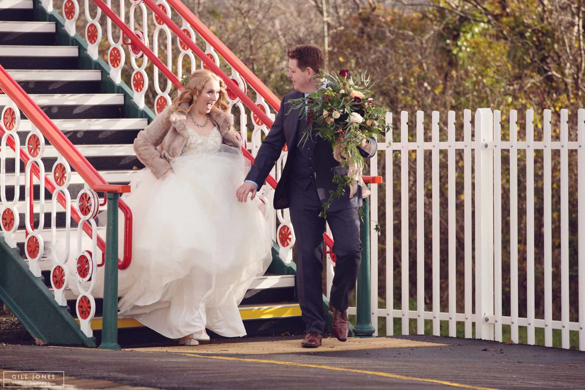 bride and groom hurrying along a train station platform