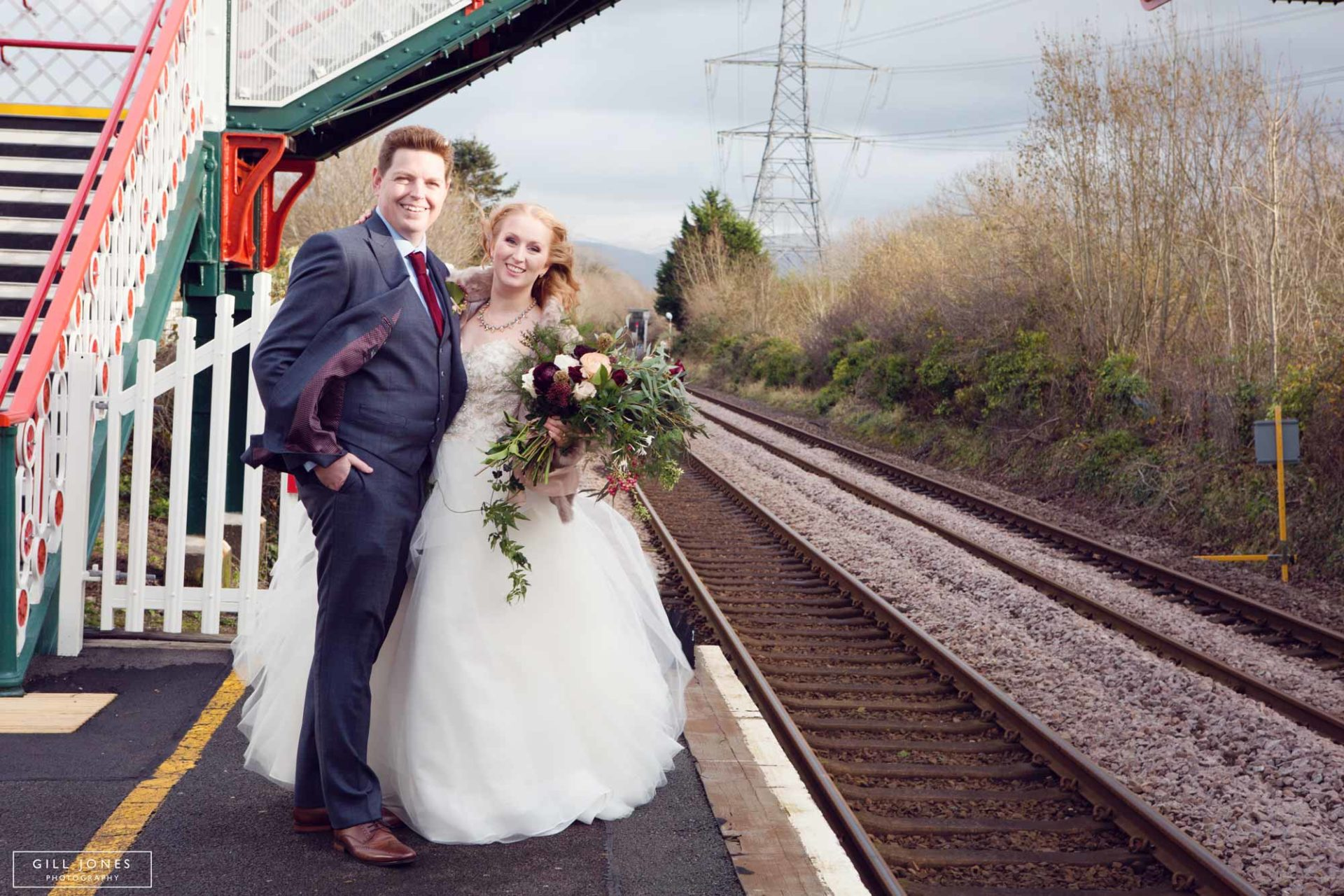 the bride and groom standing close at the rail station
