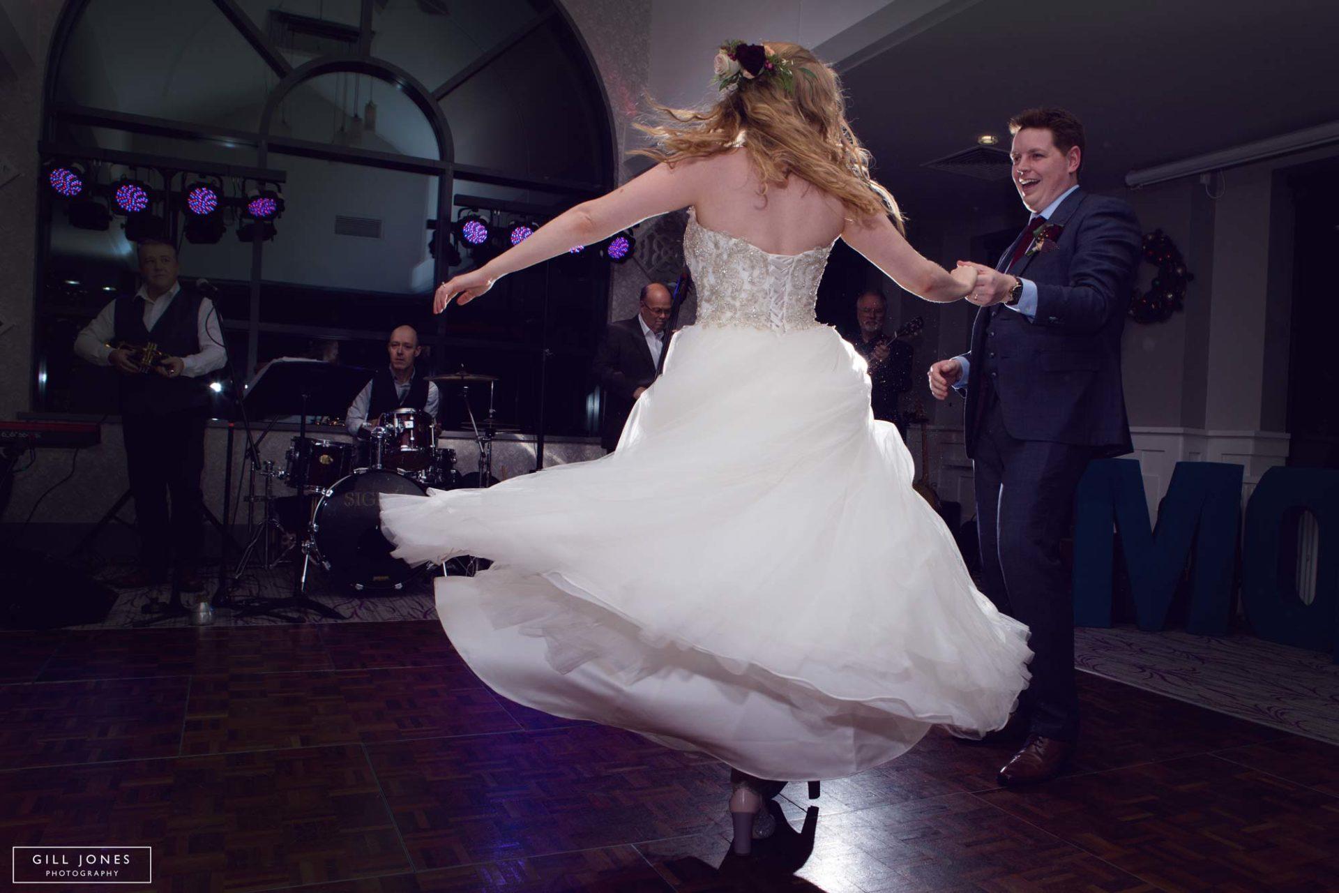 the bride twirling in her dress on the dancefloor